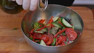 Pouring olive oil into fresh summer salad