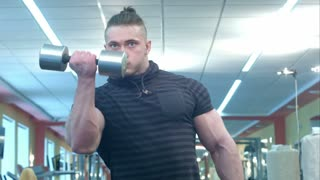 Powerful athletic man doing biceps exercise with dumbbells in a gym club