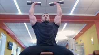 Powerful athletic man doing biceps exercise with dumbbells in a gym