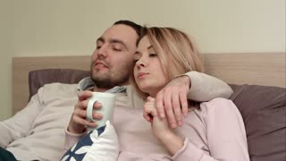 Pretty couple watching a movie at home, woman drinking tea and talking to a partner