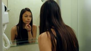 Pretty, elegant woman applying lipstick in bathroom at home