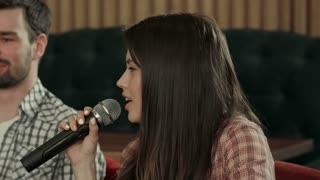 Pretty young woman singing karaoke