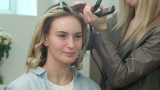 Professional hair dresser use hair straight iron straightener hair, while talking with client