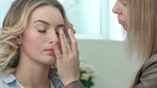 Professional make-up artist applying cream base eyeshadow primer to model eye