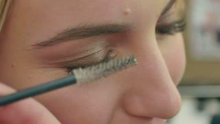 Professional make-up artist combing eyelashes of model