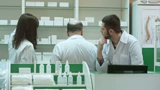 Professional pharmacist and pharmacy technician working in drugstore