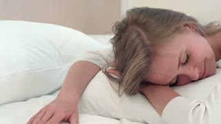 Relaxed young blonde girl sleeping on white bed at home or in hotel room