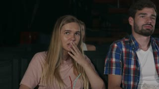 Scared girl closing her eyes with her hands watching scary movie in the cinema