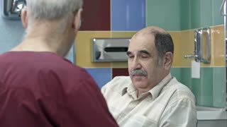Senior male doctor talking to senior man in surgery