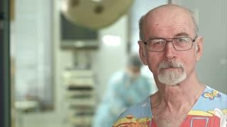 Senior mature surgeon smiling at the camera in hospital surgery examination room