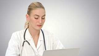 Serious female doctor working on her laptop computer on white background