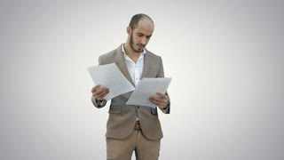 Serious young businessman standing and reading some documents on white background