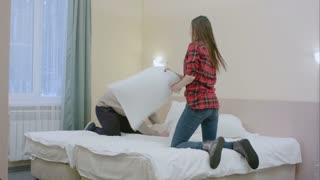 Sexy couple enjoying their pillow fight game in bed in a hotel room