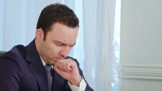 Sick young businessman coughing and blowing his nose in office