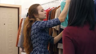 Skillful saleswoman advising client in boutique