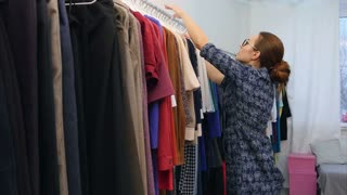 Small business owner in clothes shop checking collection