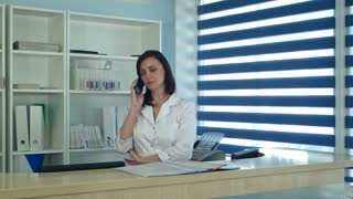 Smiling female nurse answering phone call at the reception desk