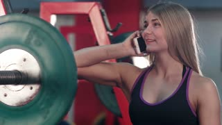 Smiling fit woman talking on the phone in the gym weight room