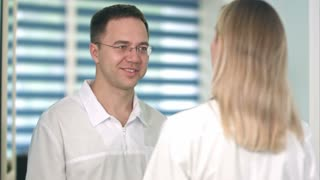 Smiling male doctor in glasses talking to female nurse