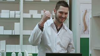 Smiling male pharmacist in white coat showing thumbs up and okey hands gesture