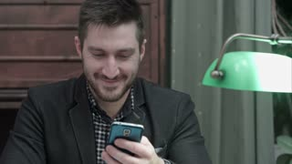 Smiling young man messaging on mobile phone