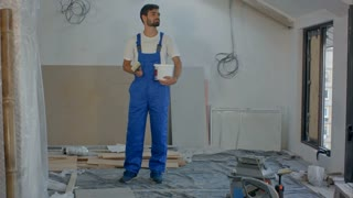 Smiling young worker standing at building house