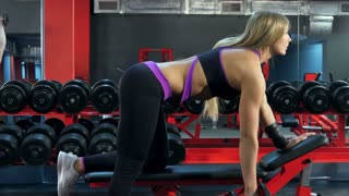 Strong female exercising with barbell in the gym