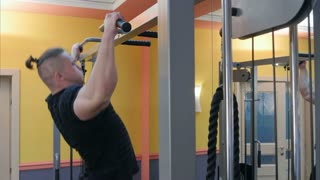 Strong man athlete doing pull ups chin ups in the gym