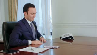 Successful young businessman counts euro bills speaking with colleague in the office