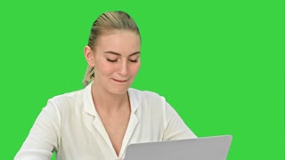 Successful young businesswoman working on laptop, writing down ideas and smiling on a Green Screen, Chroma Key