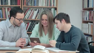 Teacher with group of students working on digital tablet in library