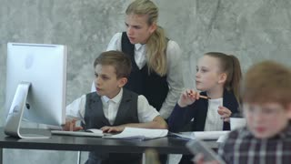 Three little children in business suits sitting at table with laptop, discussing something