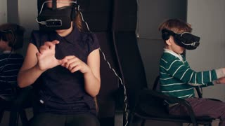 Three little kids in vr headsets enjoying virtual reality game