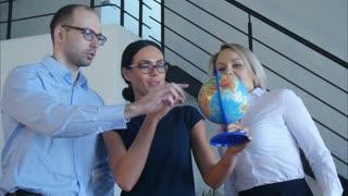 Three teachers discuss something with globe