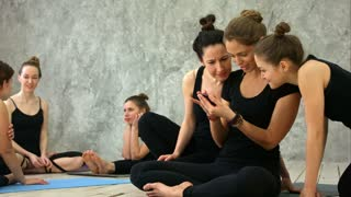 Three young women relaxing, using smartphoe, talking after workout at yoga class