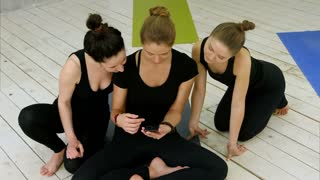 Three young women studying yoga asana using smartphone after workout at yoga class