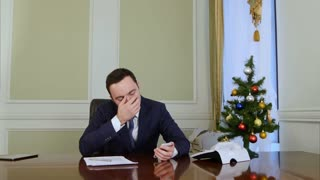 Tired businessman using cellphone and yawning