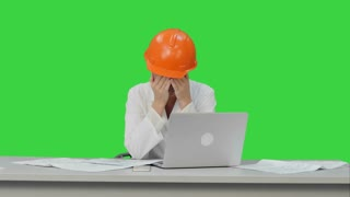 Tired young woman in safety helmet yawning and try to work on a Green Screen, Chroma Key