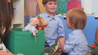 Two baby boys playing with toys in their nursery room