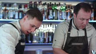Two barmanan working and discussing something at counter in bar