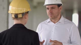 Two colleagues in the work plan discussing at a construction site