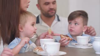 Two little boy kids having tea with pastry together with their parents