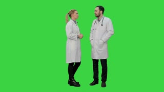 Two professional doctors talk before operation on a Green Screen, Chroma Key