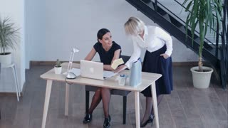 Two women working together with documents and laptop at office