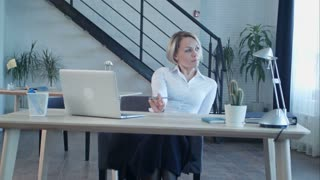 Unhappy bored woman sitting in office
