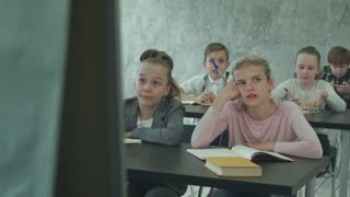 Unhappy schoolgirl in class listen to a teacher