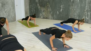 Women doing yoga sun salutation pose indoors at yoga studio