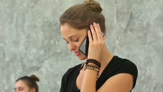 Yoga instructor speaks on the phone after training