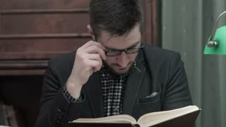 Young academic in glasses attentively reading a book