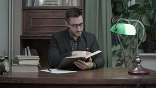 Young academic reading a book and sarcastically nodding his head